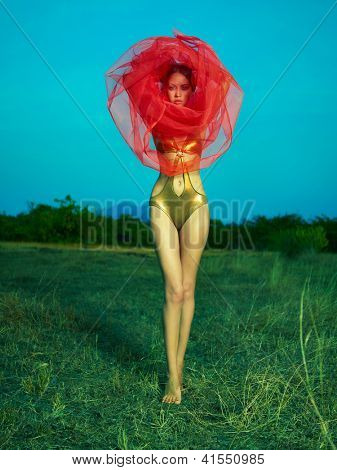 Sensual beautiful woman under the red veil on nature