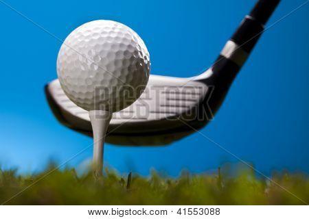 Bola de golfe na grama verde sobre um fundo azul