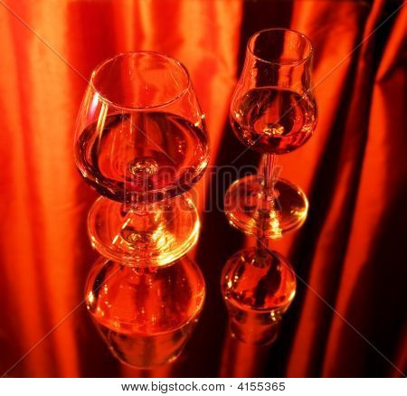 Two Glasses With Brandy On Mirror, Red Background
