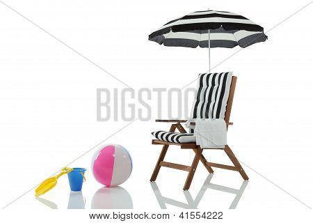 Cadeira de praia com brinquedos de praia e guarda-chuva