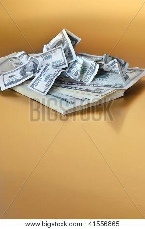 Pilha do dólar americano, coberto por notas falsas de cem dólares de tamanho pequeno. Fundo dourado.