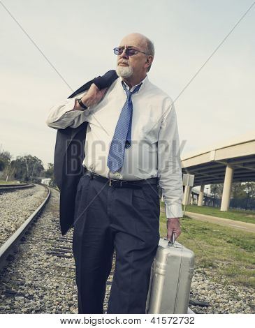 Jobless Senior Businessman Looks Upward, Walking Along Railroad Train Track With Suitcase.