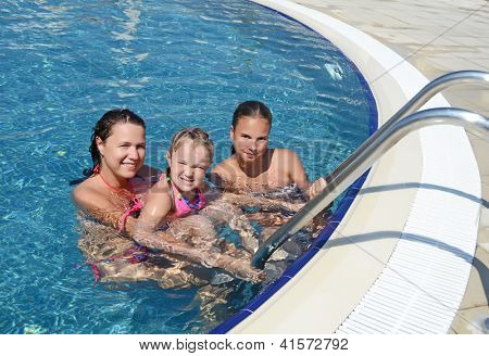 Smiling beautiful woman and her daughter have a fun in pool outdoor