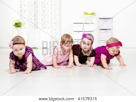 Group of four toddler girls in festive dresses crawling