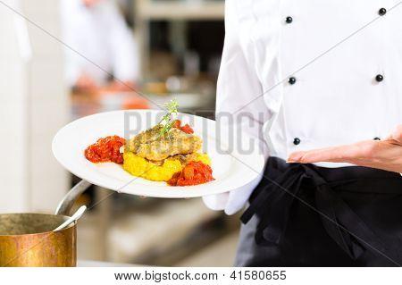 Weiblich-Chef in Hotel oder Restaurant Küche kochen, nur Hände, präsentiert sie ein Gericht auf Teller