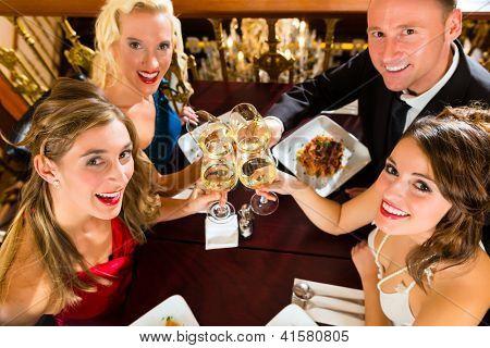 Buenos amigos para la cena o el almuerzo en un restaurante, el tintinear de vasos