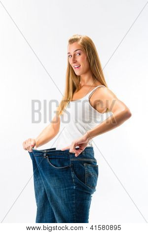 Woman standing and wearing too big pants after loosing weight