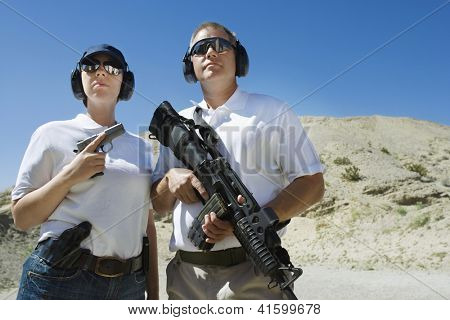 Military people with handgun and machine gun at firing range