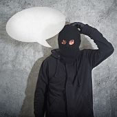 stock photo of shoplifting  - Confused burglar with speech balloonconcept thief with balaclava caught confused and without idea in front of the grunge concrete wall - JPG