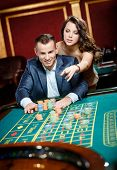 image of roulette table  - Man accompanied by woman placing bets at the casino table - JPG