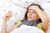 foto of high fever  - Young girl laying on the bed and feeling bad because the high fever - JPG