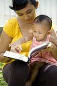 stock photo of babysitting  - asian ethnic young mother reading a book while babysitting her daughter in the park - JPG