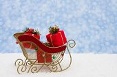 stock photo of santa sleigh  - Gold metal sleigh with presents on snow with snowflake background Santa - JPG