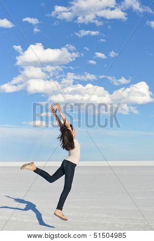 Girl jumps with vast white salt flats background in Bonneville, Utah