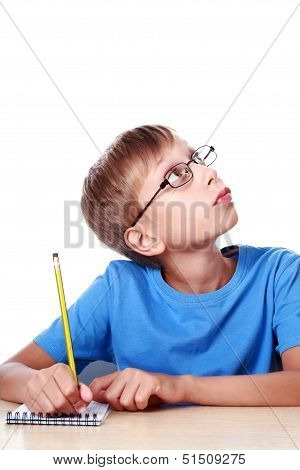 Beautiful blond schoolboy sits at a table writing in a notepad with a pencil thinking and looking as