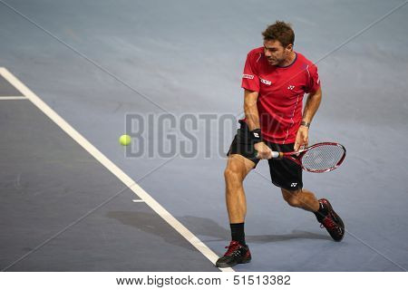 KUALA LUMPUR - SEPTEMBER 26: Stanilas Wawrinka hits a return a match against Marcos Baghdatis at the Malaysia Open 2013 tennis played at the Putra Stadium, Malaysia on September 26, 2013.