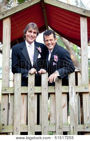 Two happy grooms in the park, following their wedding.