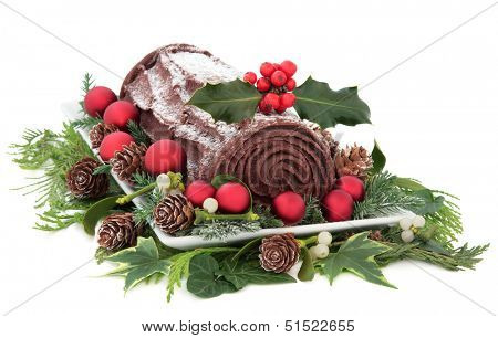 Christmas chocolate yule log cake with red baubles and holly over white background.