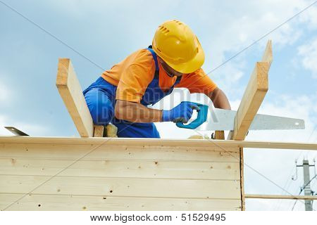 construction roofer carpenter worker sawing wood board with hand saw on roof installation work