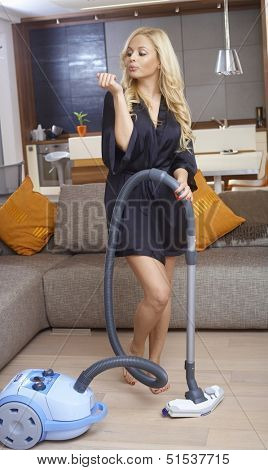 Pretty blonde woman in dressing gown using vacuum cleaner while blowing freshly polished nails.