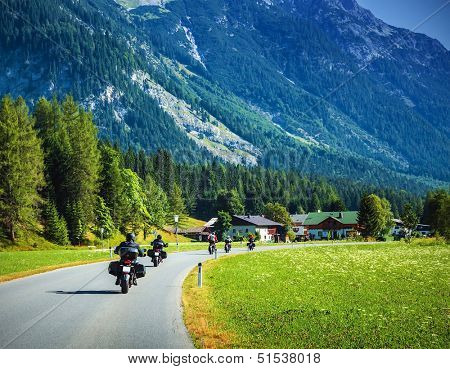 Group of motorcyclists on the road pass across mountainous village, Europe, Alps, active lifestyle, drive motorbike, extreme highway