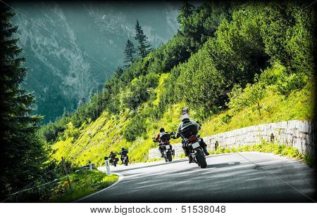 Group of moto bikers on mountainous highway, riding on curve road pass across Alpine mountains, extreme lifestyle, freedom concept
