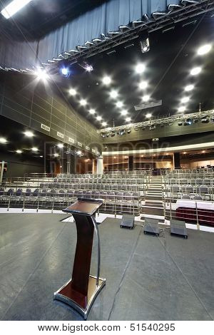 Document stand on stage and rows of seats in big black hall for business meetings.