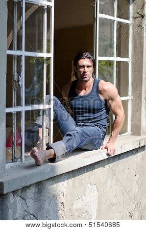 Attractive, Muscular Man Sitting On Open Window