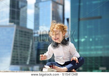 Little cute girl with red book sits on border and laughs near skys?raper at sunny day.