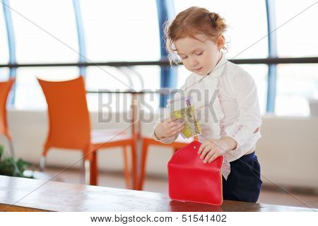 Little cute girl in white shirt stands near table in cafe and gets money from wallet.