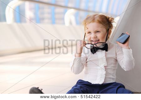 Red hair little cute girl with cell phone sits on floor and removes glasses.