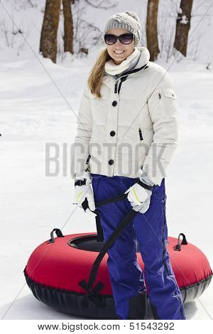 Woman having fun going snow tubing on a winter day
