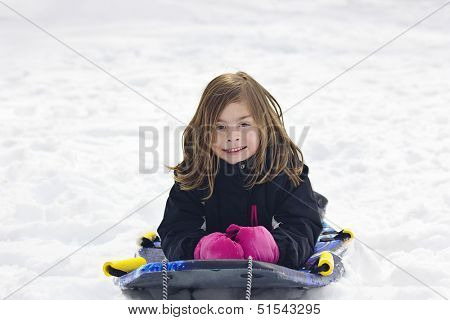 Cute Little Girl going snow sledding down a hill