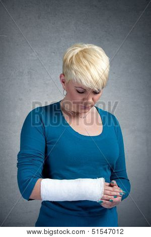 Sad woman looking at broken arm on her arm.