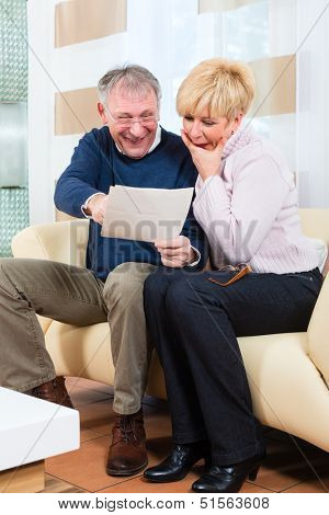 Two elderly people have received a letter, maybe they have won the first prize and its a Winning notification