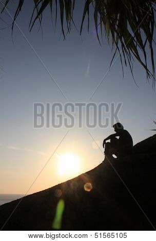 Man sitting as silhouette by the sea