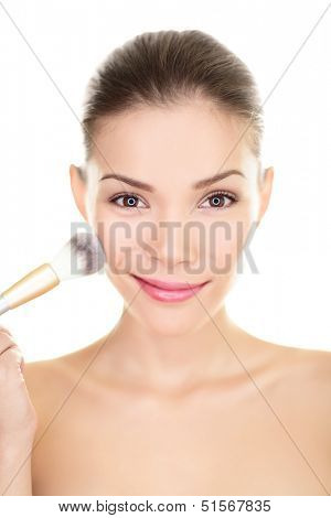 Asian beauty woman putting makeup blush on face. Chinese skincare girl applying powder with brush on cheeks, closeup smiling at camera. Mixed race Chinese Asian / Caucasian model isolated on white.
