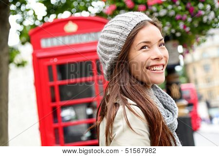 London people - woman by red phone booth. Portrait of beautiful smiling happy young female casual professional business woman walking outside in City of Westminster, London, England, Great Britain.