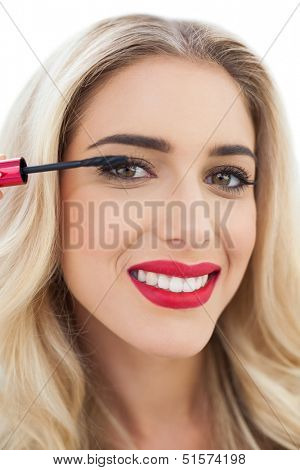 Smiling blonde model in blue dress applying mascara on white background