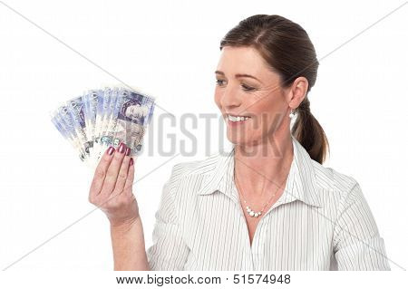 Woman Making Fan Of Pound Sterling Banknotes