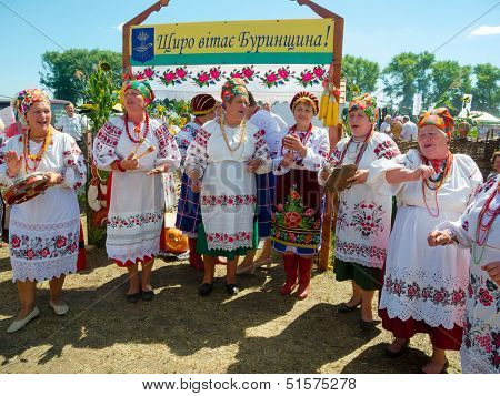 SUMY, UKRAINE - AUGUST 17: Women wearing historical costume posing in traditional village background on annual agro exhibition SUMY-2013 on August 17, 2013 in Sumy, Ukraine