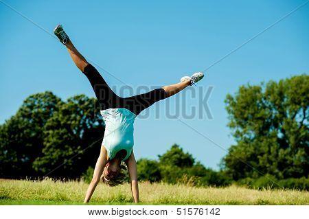 Woman Doing Cartwheel In A Field