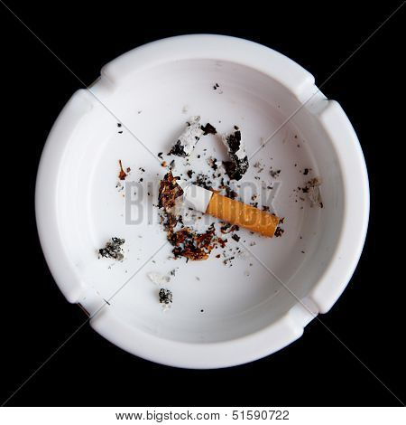 Cigarette in an ashtray on black