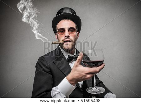 elegant man with cylinder smokes a cigar and drinks red wine