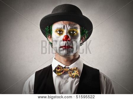 portrait of sad clown with bowler hat and red nose