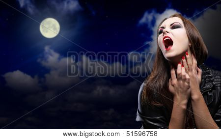 Vampire girl on night sky background