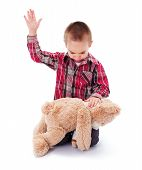 stock photo of attitude boy  - Angry little kid beating his teddy bear  - JPG