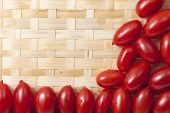 pic of oblong  - Small oblong red ripe tomatoes on a wicker wooden platter - JPG