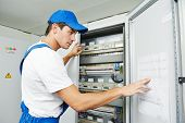 picture of fuse-box  - Young adult electrician builder engineer inspecting electric counter equipment in distribution fuse box - JPG