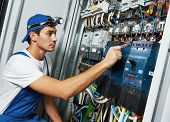 stock photo of electrical engineering  - Young adult electrician builder engineer screwing equipment in fuse box - JPG